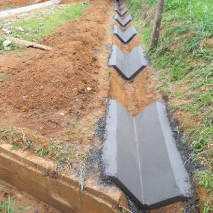 Construction des fossés bétonnés, trottoirs, parking couvert avec charpente métallique, et d'un portail